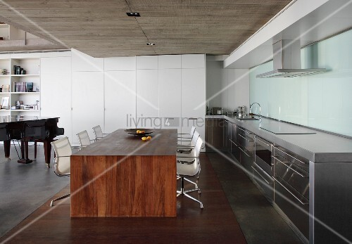 Minimalist, Solid Wood Dining Table And Classic Swivel Chairs In Open Plan  Kitchen With Concrete Ceiling