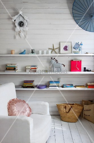 White armchair in front of white wooden wall with books & ornaments on shelves below old cuckoo clock