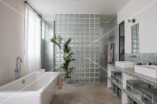 Free-standing bathtub, washstand with twin countertop sinks and shower area with glass brick partition in bathroom