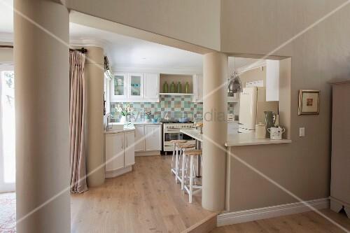 durchgang zur k che flankiert von st tzs ulen weisse einbauk che mit mosaikfliesenr ckwand. Black Bedroom Furniture Sets. Home Design Ideas