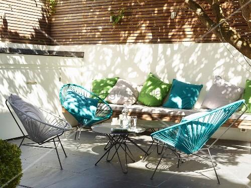 Retro Outdoor Sessel mit farbiger Seilverspannung auf sonniger Terrasse, im Hintergrund vor Brüstungsmauer grüne und blaue Kissen auf Bank