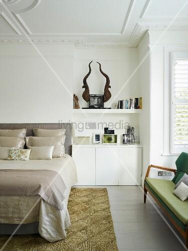 Teilweise sichtbares, elegantes Doppelbett mit drapierten Kissen, neben in Nische eingebaute Unterschränke in Weiss, auf Ablage stilisierte Trophäe, in traditionellem Schlafzimmer