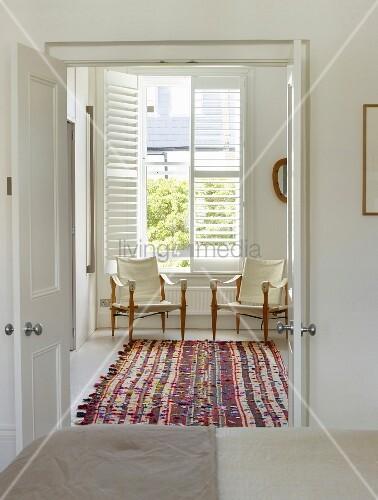 Blick durch offene Flügeltür auf buntem Teppich und filigrane Sessel mit naturfarbenem Bezug vor Fenster
