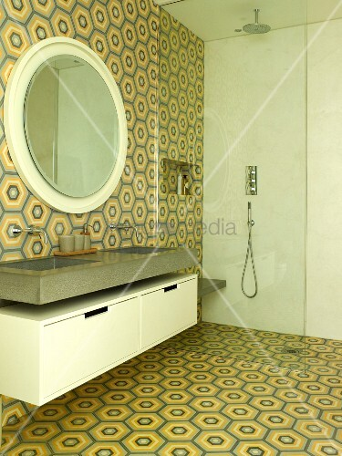 Waschtisch und runder Wandspiegel neben bodenebener Dusche mit Glas Trennscheibe im Badezimmer mit Retro Fliesen