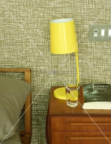 Retro Nachttischleuchte in Gelb auf Nachtkästchen aus Holz vor tapezierter Wand
