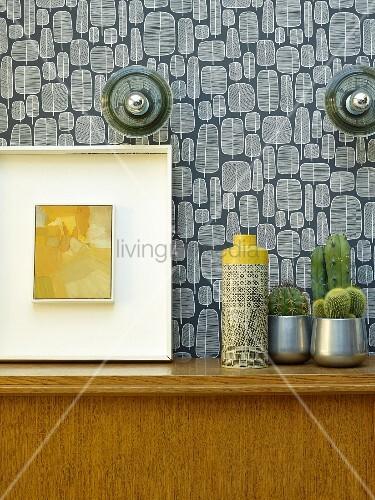 Vase neben Kakteen und Bild auf Holzschrank vor tapezierter Wand mit Retro Muster
