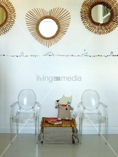 Truhe aus Geflecht zwischen Ghost Stühlen, oberhalb runde Spiegel mit strahlenförmigem Rahmen an Wand