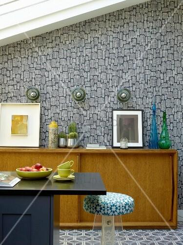Schwarze Theke und Sideboard aus hellem Holz im Fiftiesstil, vor tapezierter Wand mit Retro Muster