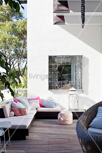 Gemütlich möblierte Terrasse mit moderner Ecksitzbank, Polstern und Kissen