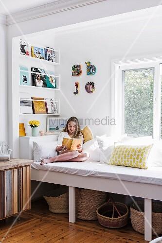 Mädchen sitzt auf einem Einbau-Tagesbett unter dem Fenster und liest, darunter ist Stauraum für Körbe