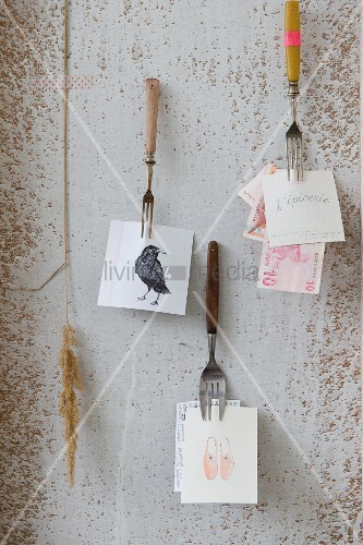 Various vintage forks nailed to wall used as holders for notes