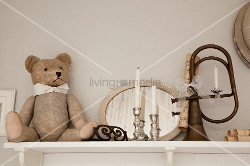 Teddy bear and silver candlesticks in front of mirror next to vintage bugle