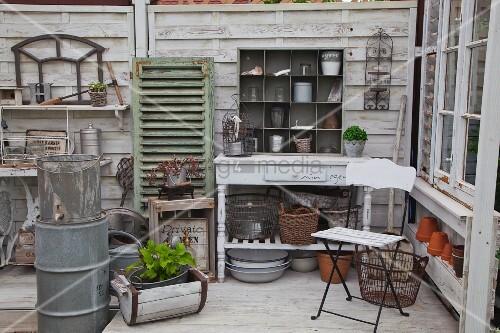 Weisser Klappstuhl und ländlicher Konsolentisch mit Blumentöpfe in Regalaufsatz im Gartenhäuschen