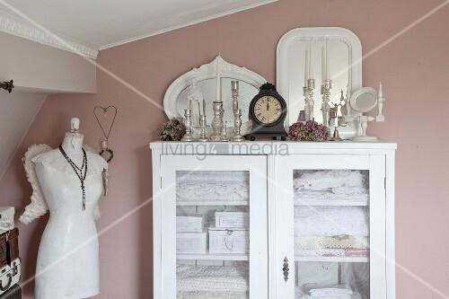 weiße Wäscheschrank mit Glastür, obenauf Vintage Kerzenhalter, seitlich Schneiderpuppe