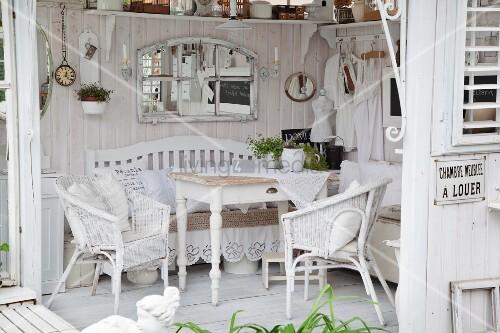 blick auf holztisch und weisse rattanst hle in shabby gartenpavillon mit weiss lasierten. Black Bedroom Furniture Sets. Home Design Ideas