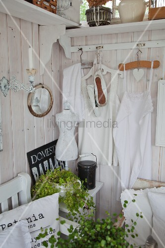 White rustic clothing hung on clothes hangers on white-stained wooden wall