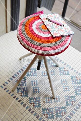 Hocker mit handgefertigter dekorativer Häkelauflage
