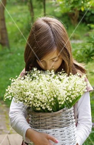 Mädchen mit grossem Maiglöckchenstrauss in Weidenkorb im Freien