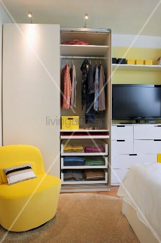 Stauraum im Schlafzimmer durch praktisches Innenleben im Kleiderschrank; gelber Sessel als sonniger Akzent vor neutralem Weiss