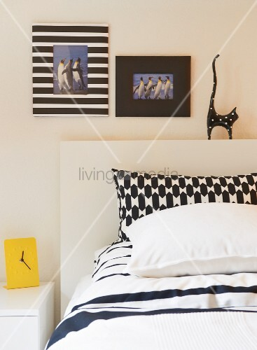 Mixture of black and white patterns on pillow covers, decorative picture frames and cat ornament on bed headboard