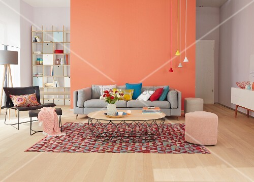 A seating area with basic furniture, brightly coloured pendant lamps against a light red wall and complementary accessories