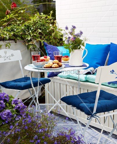 A table laid on a sunny balcony with lightweight, space-saving folding furniture and a bench chest