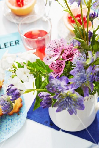 A bunch of delicate flowers, cakes and juice on a table laid on a summery balcony