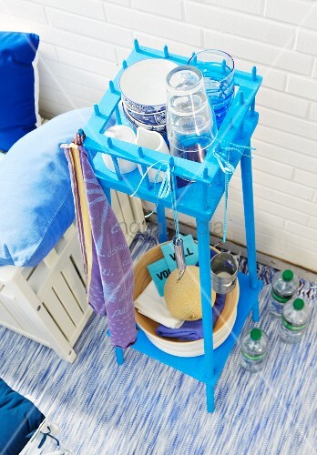 A recycled, bright blue plant stand being used outside table on a balcony