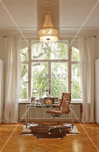 Retro desk chair and modern table below window, animal-skin rug on herringbone parquet and chandelier
