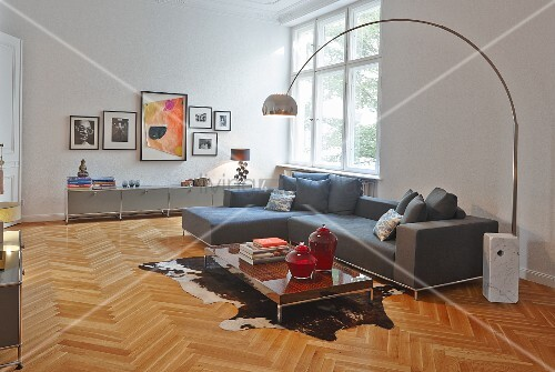 Retro arc lamp with stone base next to modern sofa combination and low table on animal-skin rug on herringbone parquet in spacious living room