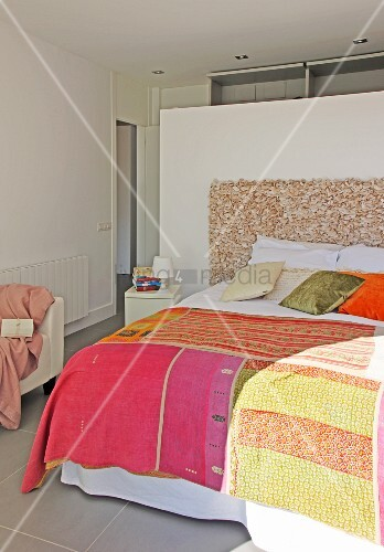 Patchwork bedspread on double bed against partition in bedroom