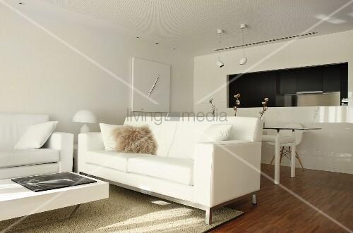 White designer furniture in open-plan interior with dining area next to kitchen pass-through