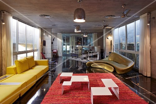 Delicate coffee table in white-painted metal on red rug, yellow sofa and golden sofa by Zaha Hadid