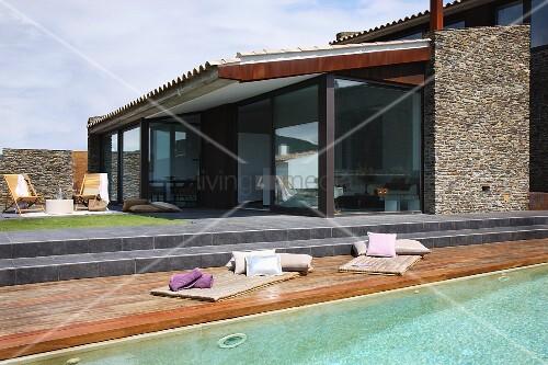 Zu Sonnenterrasse hin aufgeglaster Ferienbungalow mit Natursteinfassade; Steinstufen zu Sonnendeck am Pool im Vordergrund