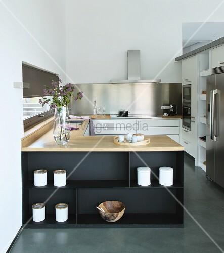 Elegante Einbauküche mit Küchentheke, puristisch mit Dosen und Schale aus Olivenholz dekoriert