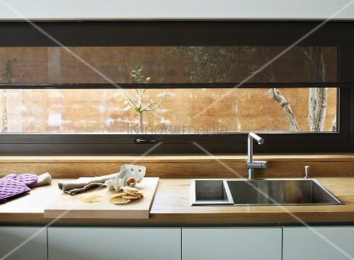 Eckige Edelstahlspüle in Küchenarbeitsfläche mit Naturholzplatte, darüber ein Fensterband mit transparentem Springrollo