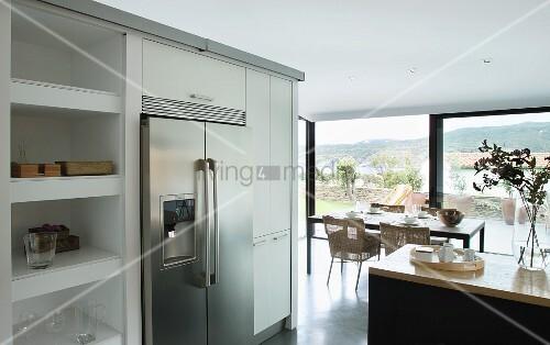 Doppeltüriger Kühlschrank aus Edelstahl, flankiert von Küchenschränken und Regal; im Hintergrund Essplatz vor Panoramafenster