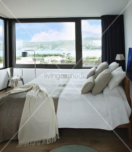 Doppelbett mit naturfarbenen Bezügen in Schlafzimmer mit Landschaftsblick durch Übereck-Panoramafenster