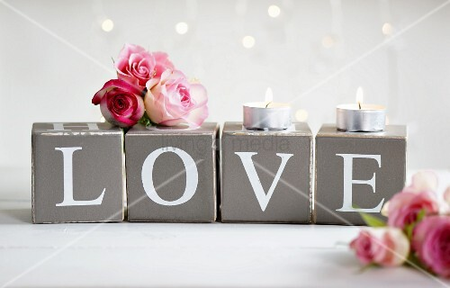 Pink roses and tealights on cardboard cubes printed with letters spelling 'LOVE'