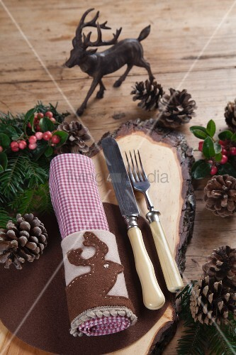 Rustic wooden board and hand-crafted felt napkin ring with appliqué stag motif on festively decorated wooden table