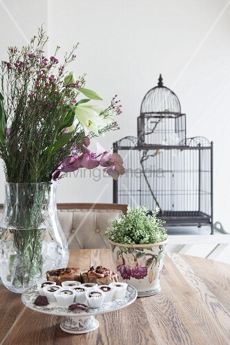 Planter, bouquet and cake stands on dining table in front of vintage-style birdcage