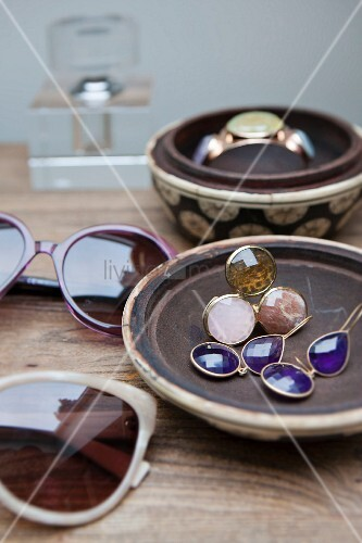 Sunglasses and jewellery in ceramic bowls on wooden table
