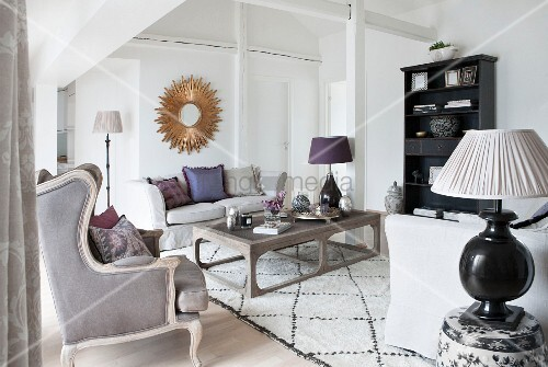 Elegantly furnished room with sloping roof, coffee table, antique armchair and table lamps
