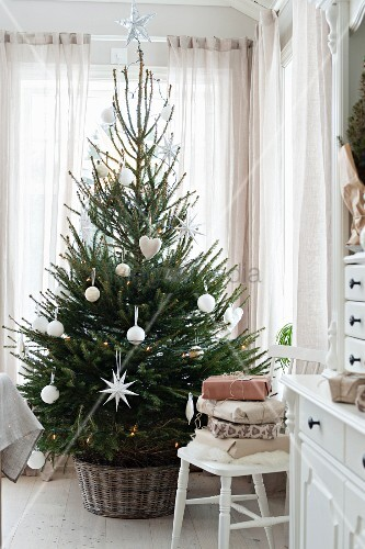 Christmas tree with white decorations in front of window