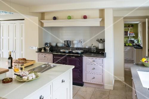 Offene Küche mit Kücheninsel und verschiedenfarbigen Schrankfronten ...