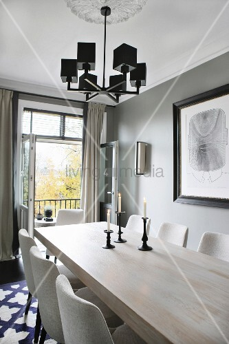 Lit candles in candlesticks on wooden table below pendant lamp with black lampshades in front of open balcony door