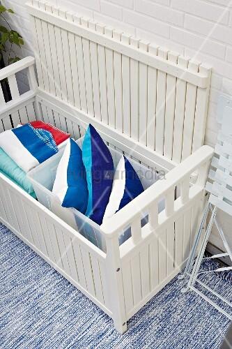 weiße Gartenbank mit Stauraum für Kissen und Decken