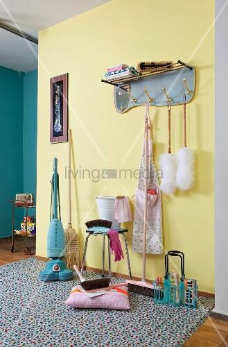 Putzutensilien im Retro Look auf gemustertem Teppich vor gelb getönter Dielenwand mit Hängegarderobe