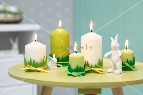 Easter arrangement in shades of green; candles with grass motif trim and rabbit ornaments on small, round table