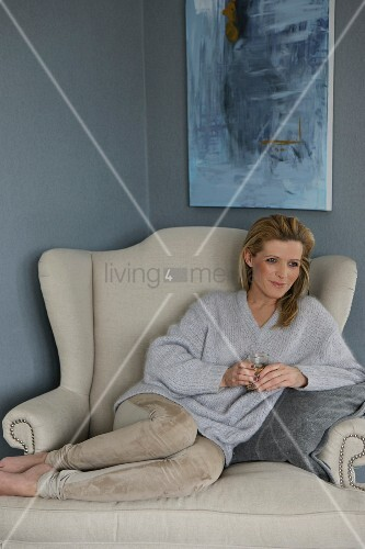 Woman with glass of tea sitting on elegant, comfortable armchair below modern painting on slate grey wall